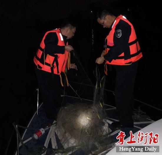 ▲渔政执法人员清理没缴的网具