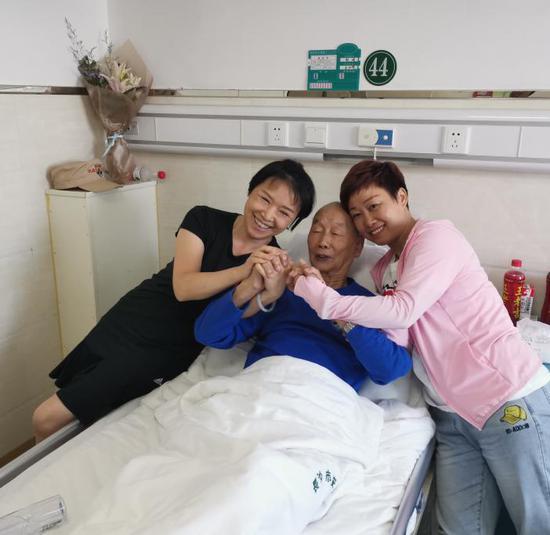 8 月 27 日,长沙市按摩骨科医院,湖南老兵之家的志愿者看望在医院休养的杨怀亮(中)。
