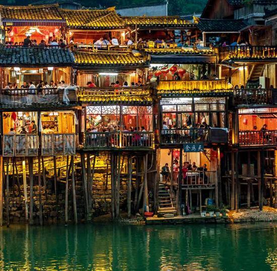 (沅江支流沱江之畔,宾客盈门的凤凰古城吊脚楼。郑安戈 摄)