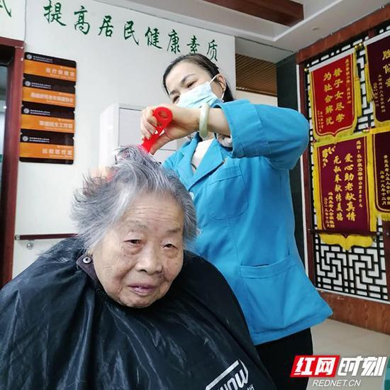 3月17 日,康乃馨韶山路社区居家养老服务中心内,护理员姚运娥为老人修剪头发。