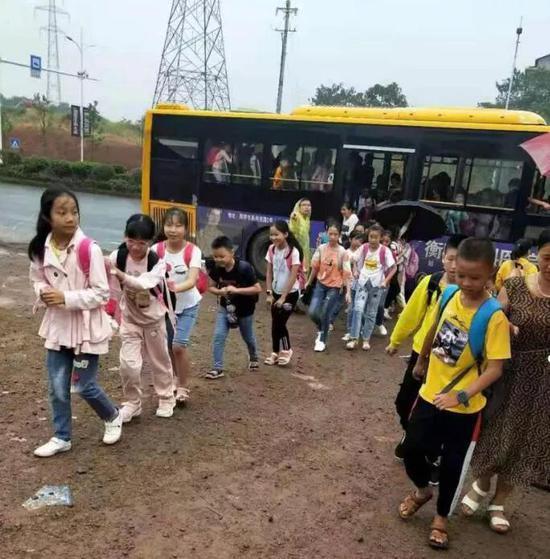 ▲小学生们高兴地走下车,前往新学校
