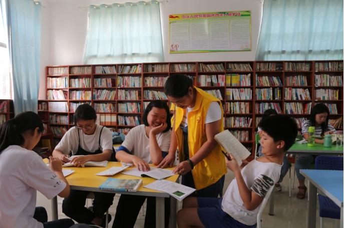 7月16日,刘利群(右二)在与爱心书屋内的学生们交流。