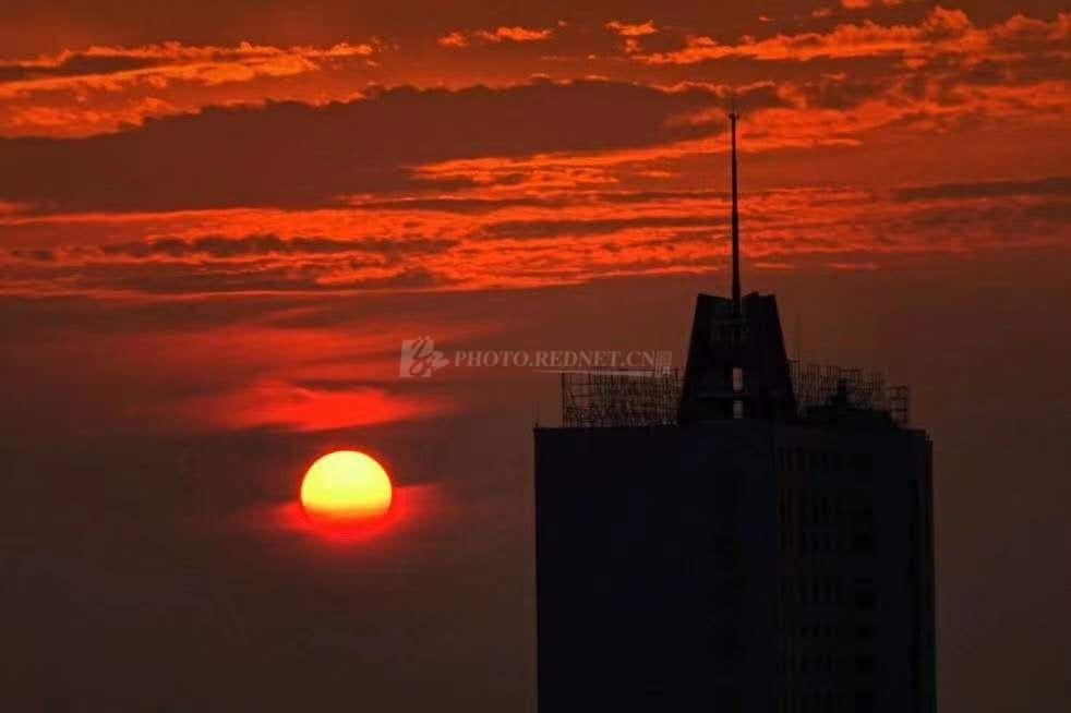 """7月30日,太阳升起,时隐时现,""""点燃""""了云层,偶尔像只眼睛在偷看我喝早茶。图/岑庆良"""