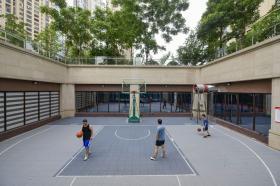 6月21日,保利西海岸小区,小区业主在自己众筹修建的篮球场上打篮球。 图/记者杨旭