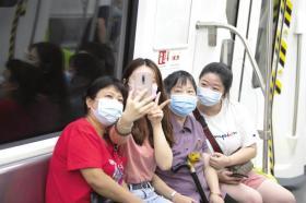 长沙地铁3号线,家住恒大雅苑的老人李萍在两个孙女的陪同下体验地铁出行。
