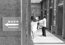 湘域国际中心,东门旁的告示提示市民在早高峰可以走南向步梯。图/记者张云峰