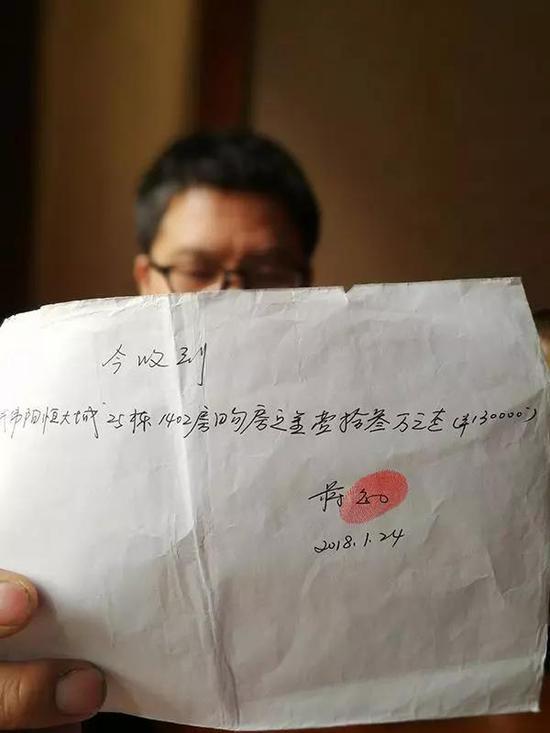 受害人武伟阳出示交了13万元购房定金的收条。 澎湃新闻记者 朱远祥 图