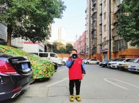 近日,长沙市天心区金盆岭街道天剑社区,喻天羿拿着喇叭宣传防疫知识。图/受访者提供