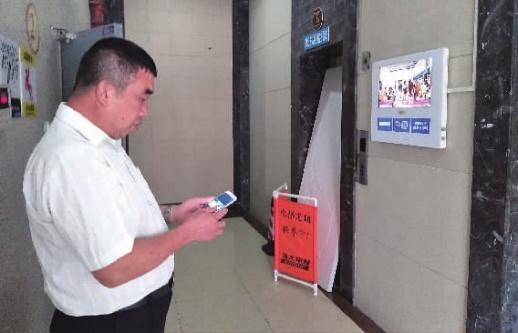 5月23日上午,长沙市天心区万芙锦城小区5号楼1单元2楼电梯间,物业人员在被损坏的电梯前查看。记者杨昱摄