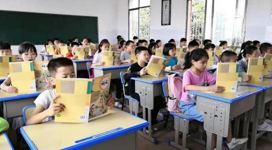 ▲雁西小学的学生们高兴地打开了新课本