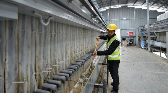 1月7日,在王家河水环境综合治理工程项目部内,工人在板框压滤机前清理压滤泥浆后剩余的淤泥。新华社发(陈振海摄)