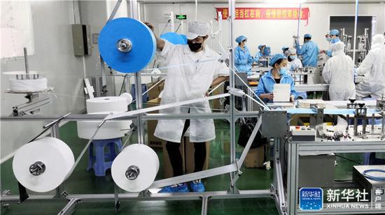 工人在深圳长盈精密技术股份有限公司口罩生产线上作业(3月2日手机拍摄)。新华社记者 周科 摄
