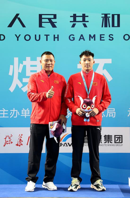 罗翔(右)获得2019年全国第二届青年运动会游泳比赛男子体校组乙组50米仰泳亚军,与教练(左)罗立军合影。陈放 摄