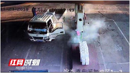 曲河加油站内,当班员工用灭火器扑灭火苗。