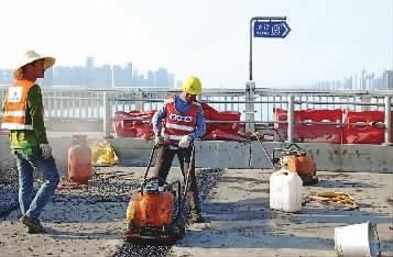 8月19日,记者在施工现场看到,橘子洲大桥行车道已完成沥青摊铺,并已划好交通标识,焕然一新,一眼望去桥面显得很平整。工人正在进行无缝伸缩缝施工(小图)。记者陈月红摄