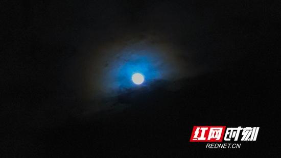 一轮明亮的圆月挂在缥缈的云层之上,周围闪耀着彩色的光环