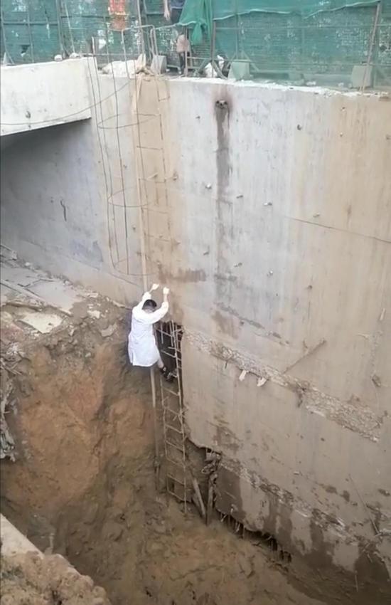 8 月 25 日,隆回县桃洪中路一处建筑工地,医生宋东阳顺着简易梯子爬下去,准备救治伤员。图 / 受访者提供