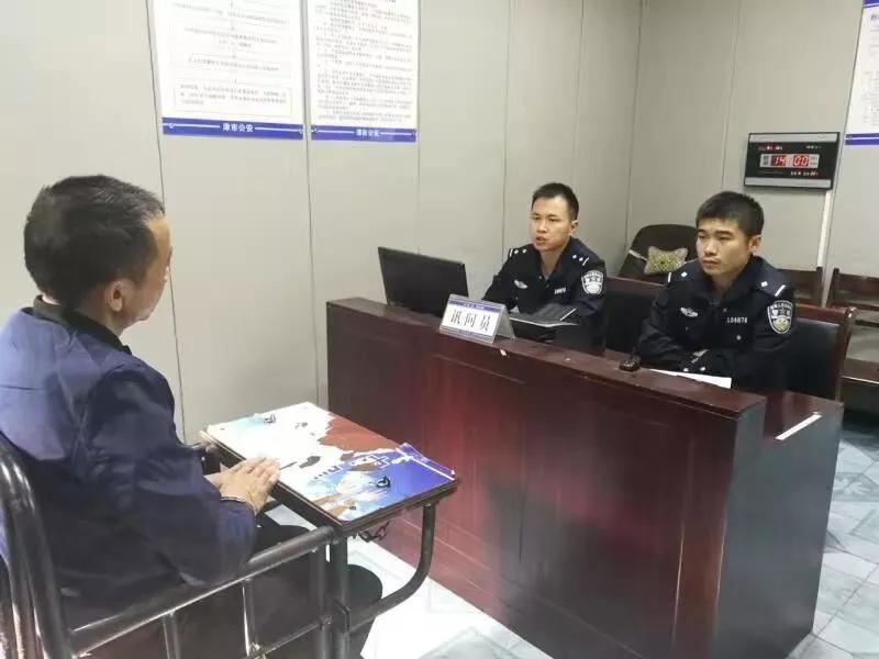 民警对嫌疑人喻某进行询问。