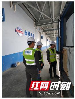 工作人员在中外运长沙铁路北站仓库进行木材集装箱卸货。