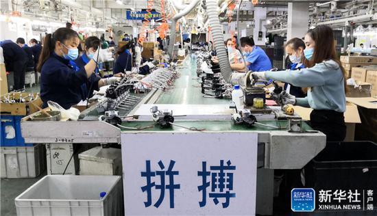 ↑工人在艾美特电器(深圳)有限公司的电风扇生产线上忙碌(3月2日手机拍摄)。新华社记者 周科 摄