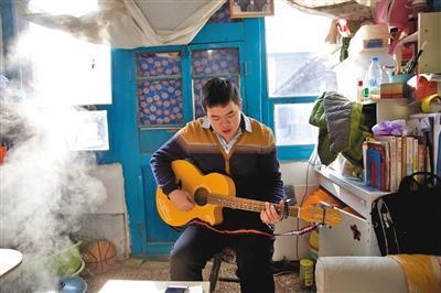 宇航在住处拿起吉他弹起新学的《爱的罗曼史》。新京报记者 郑新洽 摄