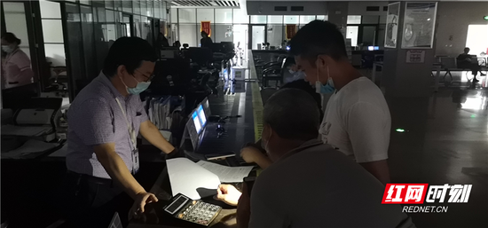 停电不停业务,窗口工作人员用手机照明继续为群众办事。