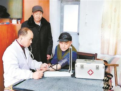 冷孟光现在把时间和精力投入到乡村医生工作中。图为冷孟光到兰溪镇敬老院义务为老人们量血压、测血糖,免费送药上门,为老人们服务。龙焕明 摄