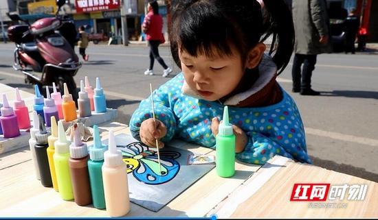 小萱萱认真地涂鸦着蝴蝶。
