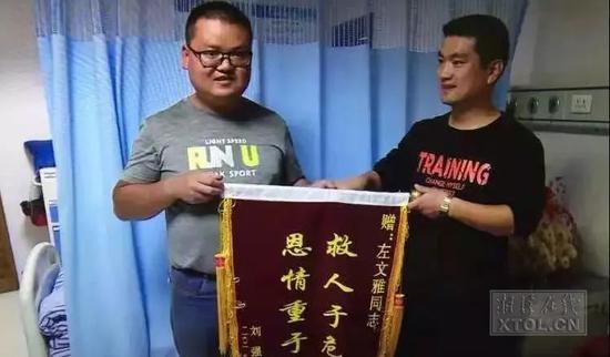 车主刘强将一面锦旗送给左文雅(右)