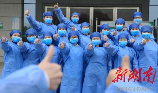(3月2日,衡阳市南华大学附属南华医院,康复的新冠肺炎确诊患者竖起大拇指给医务工作者点赞。廖红伍 曹正平 摄影报道)