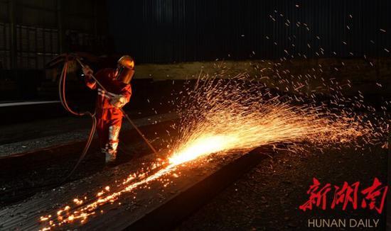 (4月29日,华菱涟源钢铁有限公司冷轧成品库房内,技术人员对钢坯进行修磨。刘新山 摄)