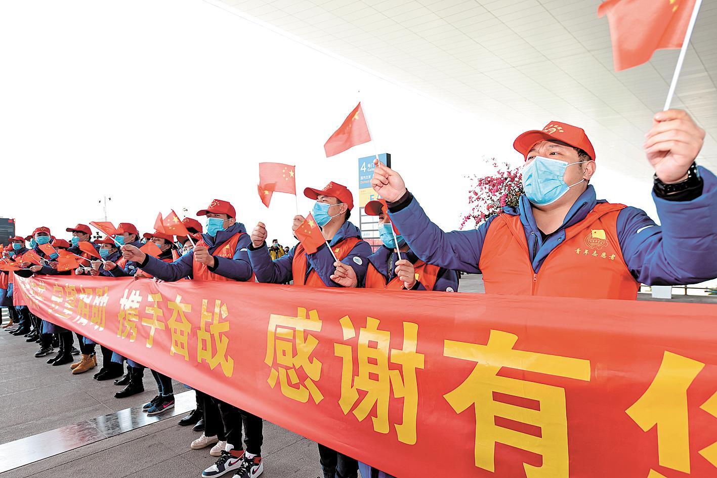 3月17日,武汉天河机场,全国各地援鄂医疗队准备乘飞机离开武汉。市民代表和志愿者在机场大厅门口向他们致敬。(湖北日报全媒记者 李溪 摄)