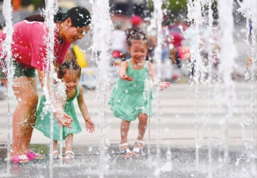 """7月3日傍晚,长沙市步步高梅溪湖新天地广场,市民在喷泉旁游玩享受清凉。当天起,长沙开启""""桑拿模式"""",最高气温升至36℃,市民外出注意防暑降温。记者 郭立亮 摄"""