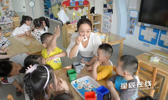 (老师在课堂上引导孩子们对不同垃圾进行分类。资料图)