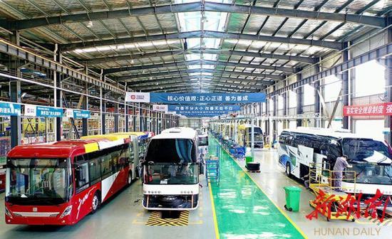 (大暑时节,位于常德经开区的常德中车新能源汽车有限公司装配车间,工人们正在装配车辆。卜云 摄)