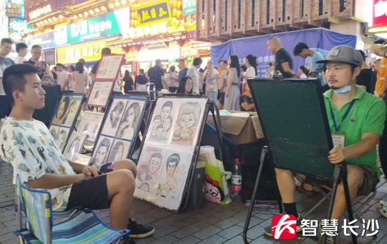 图为黄兴路步行街上的街头艺人(右)在为游客画肖像(剑裘 摄)