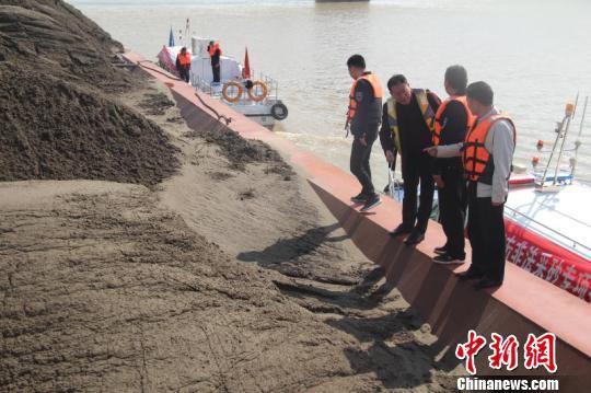 执法大队核查满载砂石的大型货船。 曹天舒 摄