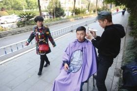 3月12日,长沙韶山南路,宋岚在人行道为顾客理发。图/记者杨旭