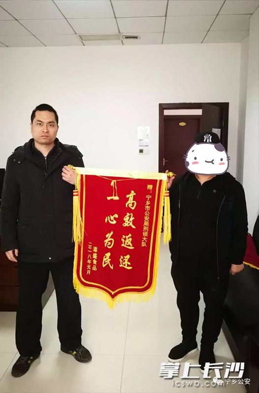 张某(右)向派出所民警送锦旗。