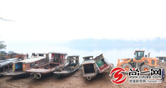 集中拆解现场,挖机正将被拆解的船舶统一排列在河滩上。记者 王浪 摄