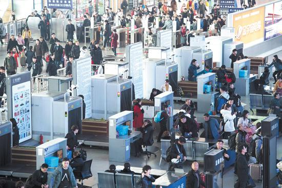 昨日,长沙火车南站迎来了客流高峰,众多旅客踏上返程路。人脸识别等系统的应用,大大加快了旅客安检速度。长沙晚报记者 黄启晴 摄