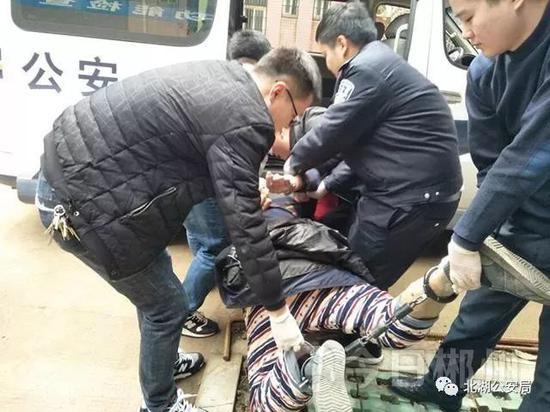 装死的胡某,被民警抬上警车