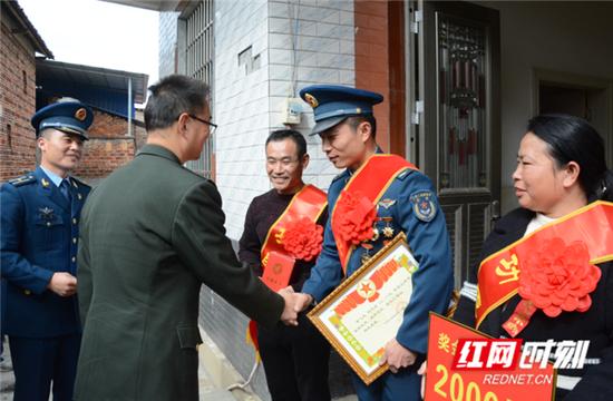 在军属家中,军地相关部门负责同志向取得荣誉的立功受奖军人表示祝贺。