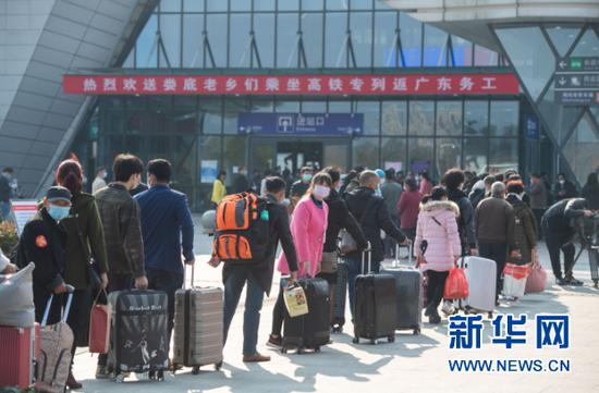 2月24日,在娄底南站,返岗复工人员排队进入火车站。