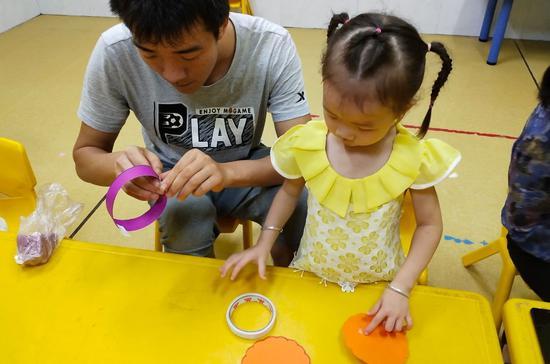 孩子们与父母共同完成手工任务。