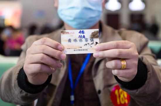 2月24日,在娄底南站候车室,一名返岗复工人员展示自己的旅客证。