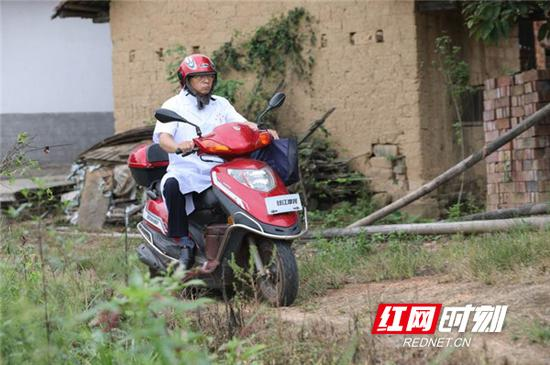 陈和平骑着摩托车行走在乡间小道上。