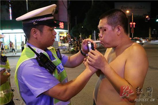 图:执勤民警对驾车男子进行呼气式酒精测试