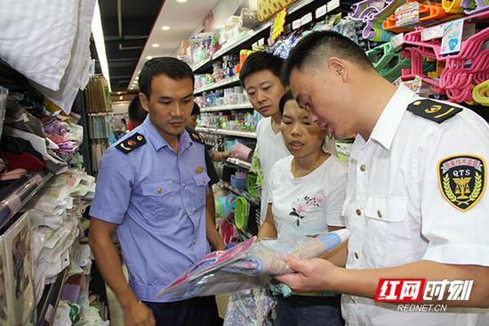 执法人员对校园周边的便利店进行纤维制品的检查。