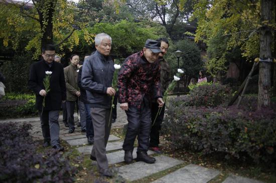 为纪念活动献花的张靖武老人及专家、志愿者。图/郑鹏